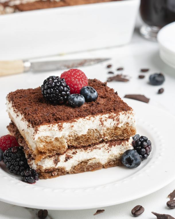 A slice of delicious creamy no-bake tiramisu is topped with fresh plump berries