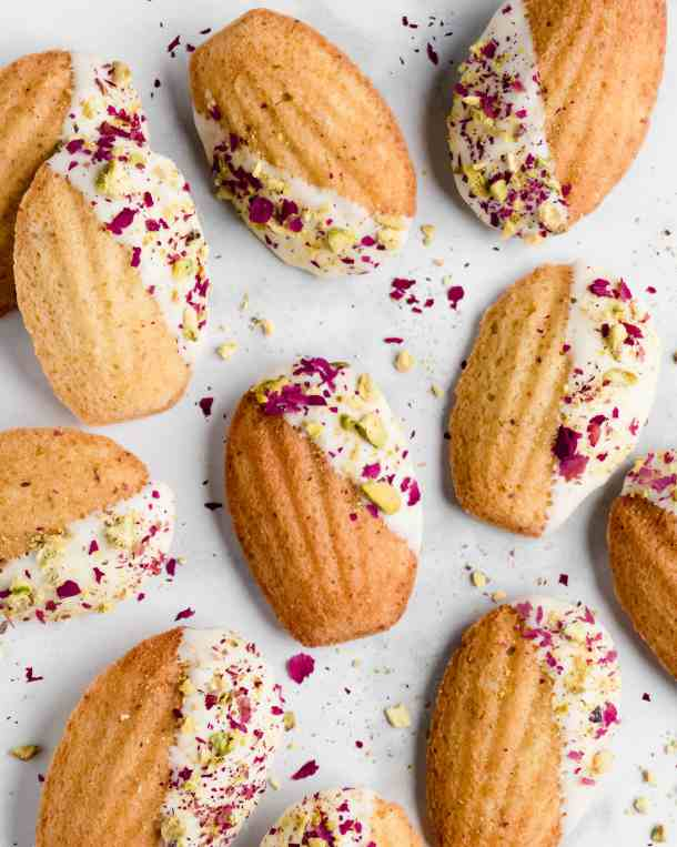 Pistachio madeleines made with rose water and dipped in white chocolate