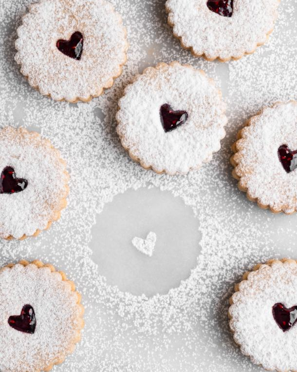 Linzer Cookies dusted with confectioners sugar and filled with raspberry jam