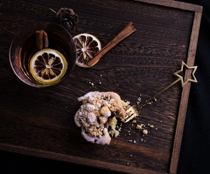 birds eye view of crumble top mince pie and glass of brandy next to it with cinnamon sticks and dried lemon slices on dark wood tray with golden star fork