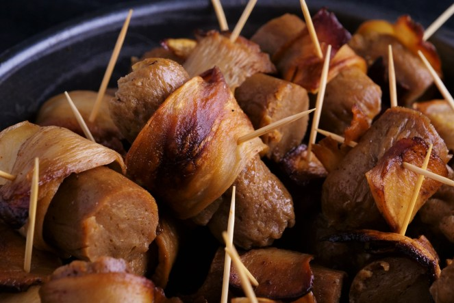 close up of golden brown seitan sausages wrapped in smoky grilled bacon made of mushroom