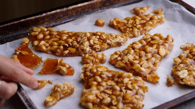 crunchy golden brown peanut brittle on metal baking tray covered with white parchment paper and hand coming into to take shards of sugar toffee shards