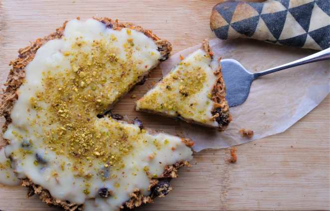 round carrot cake with cream cheese frosting and pistachioswith slice being taken using silver cake slice