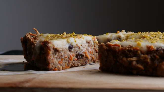 slice og healthy vegan carrot cake with raisins and carrot shreds and white frosting on wooden board