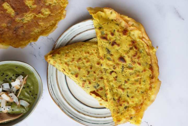yellow gram flour pancakes on white pottery plate on white marble surface next too grey bowl of green sauce and an open pancake