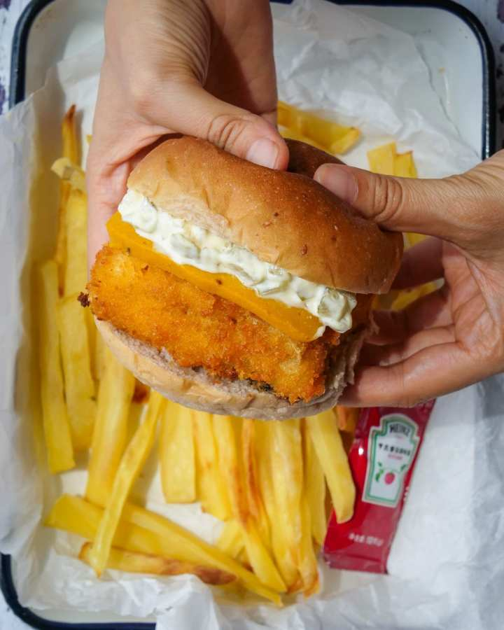 hands holding burger filled with breadcrumb coated tofu fillet, orange cheese slice, tartar sauce above fried and ketchup