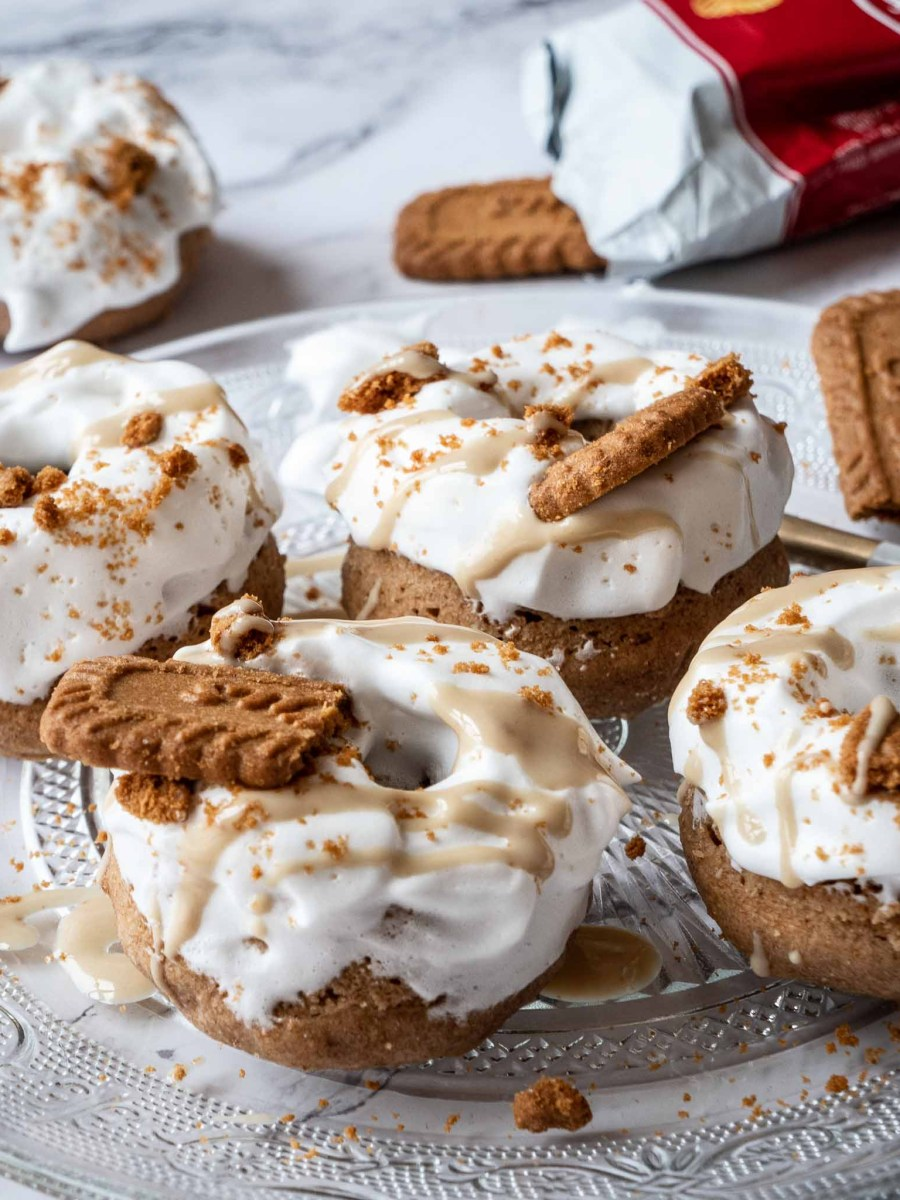mini wholewheat doughnuts covered in white fluffy frosting, caramel drizzle and biscoff cookies on glass plate