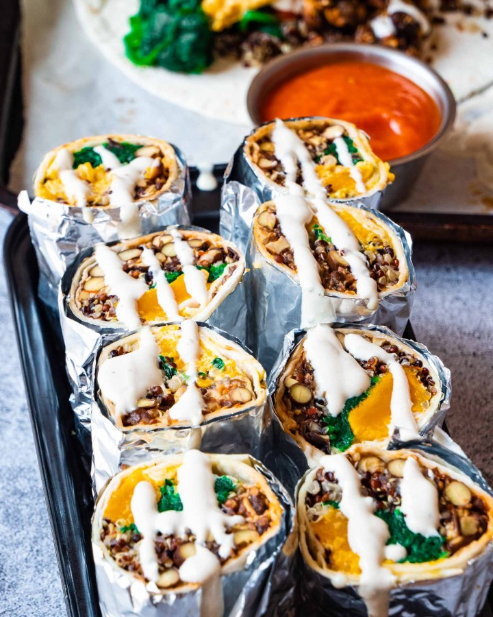 several burritos cut in halves filled with pumpkin , spinach and black beans drizzled in creamy tahini sauce wrapped in foil stuffed into loaf tin