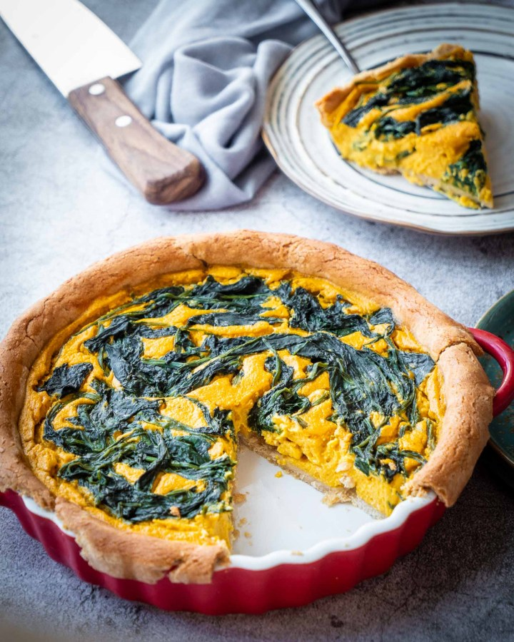 vegan pumpkin and spinach quiche baked in red quiche with slice removed on stone surface next to plate with slice on