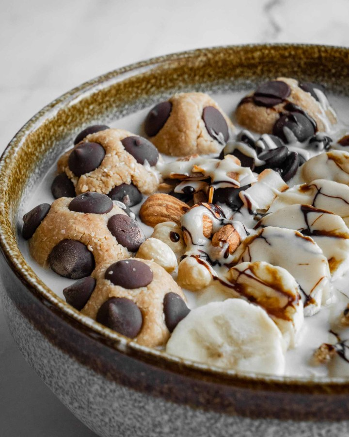 porridge bowl topped with large cookie dough calls, almonds, bananas and chocolate sauce
