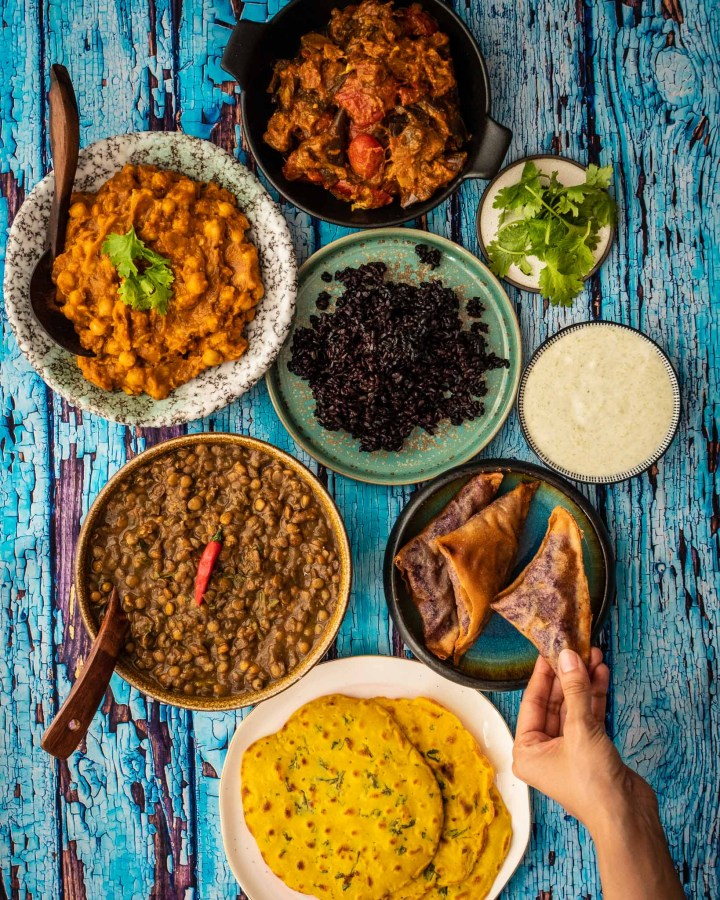 flatlay of 8 different indian food dishes in various pottery bowls on rustic blue wood board