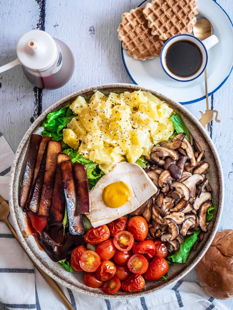 large rustic bowl filled with vegan runny eggs, vegan bacon with potato salad, mushrooms, tomatoes and green salad on white wooden table next to coffee cup