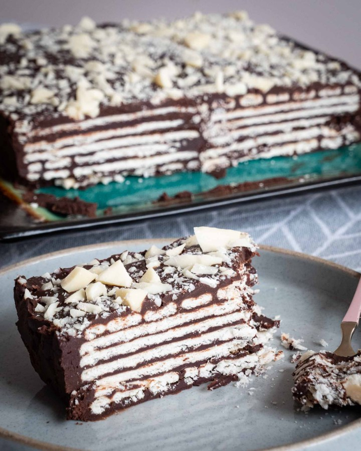 rectangular slice of kalter hund vegan biscuit chocolate layered dessert on grey rustic plate with large whole cake behind it