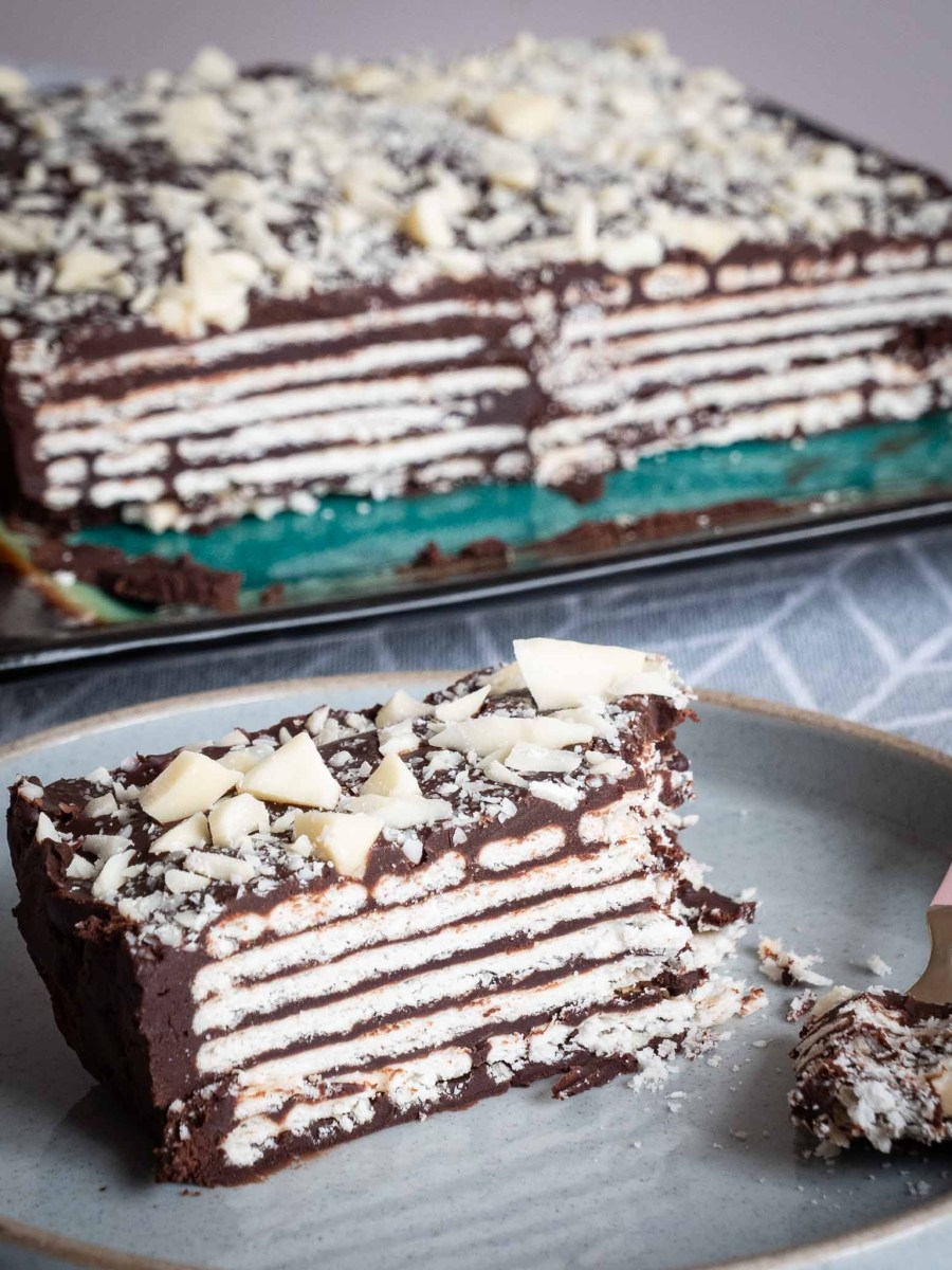vegan kalter hund with layers of crisp rectangular cookies between layers of dark chocolate ganache sliced down centre