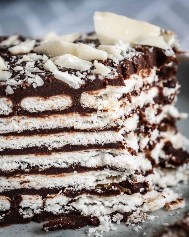 close up of white biscuit layers sandwiched between several layers of dark chocolate sprinkled with white chocolate chunks