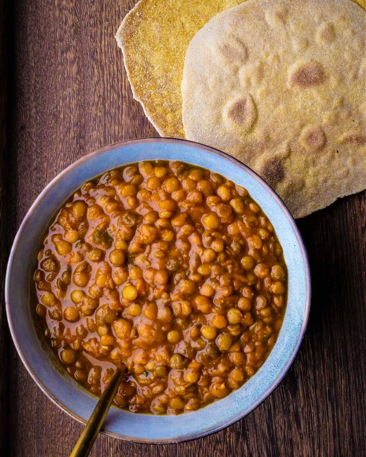 bowl of lentil curry on rustic wooden board next to pile of chapattis