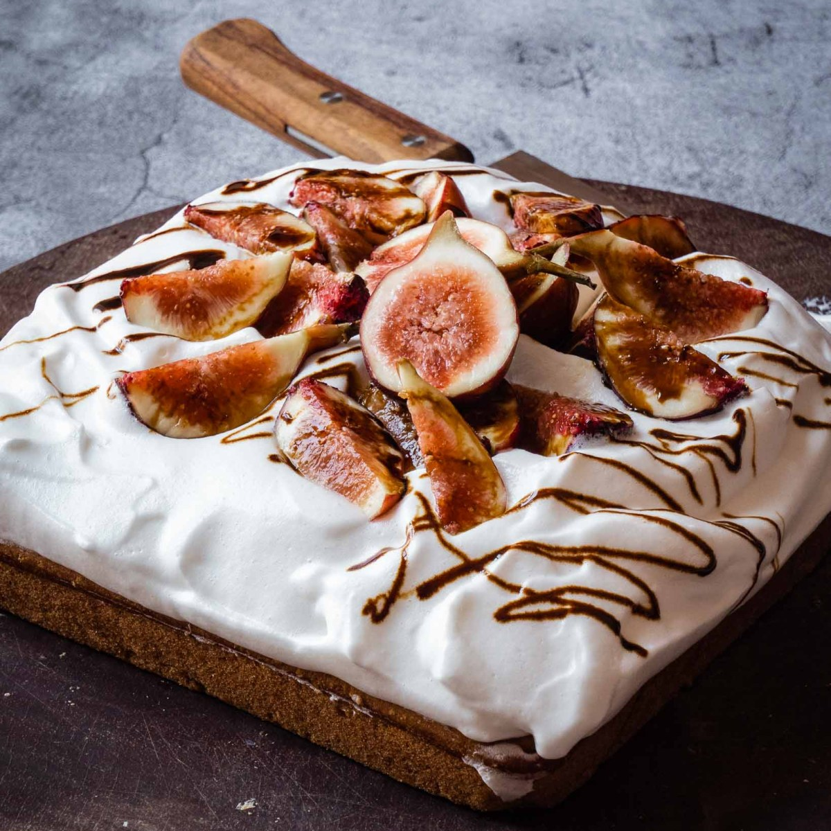 square shaped olive oil cake topped with aquafaba vegan cream frosting, fresh figs and date syrup on dark wood board on stone table