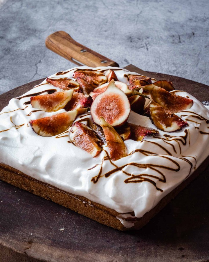 large square batch vegan olive oil cake topped with fluffy cream, drizzled with date syrup and piled with fresh sliced figs