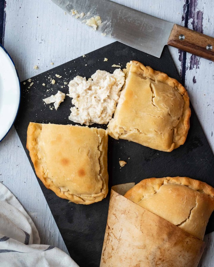 vegan cheese and onion pastie cut in half with creamy filling oozing out next to another pasty and knife on black slate board