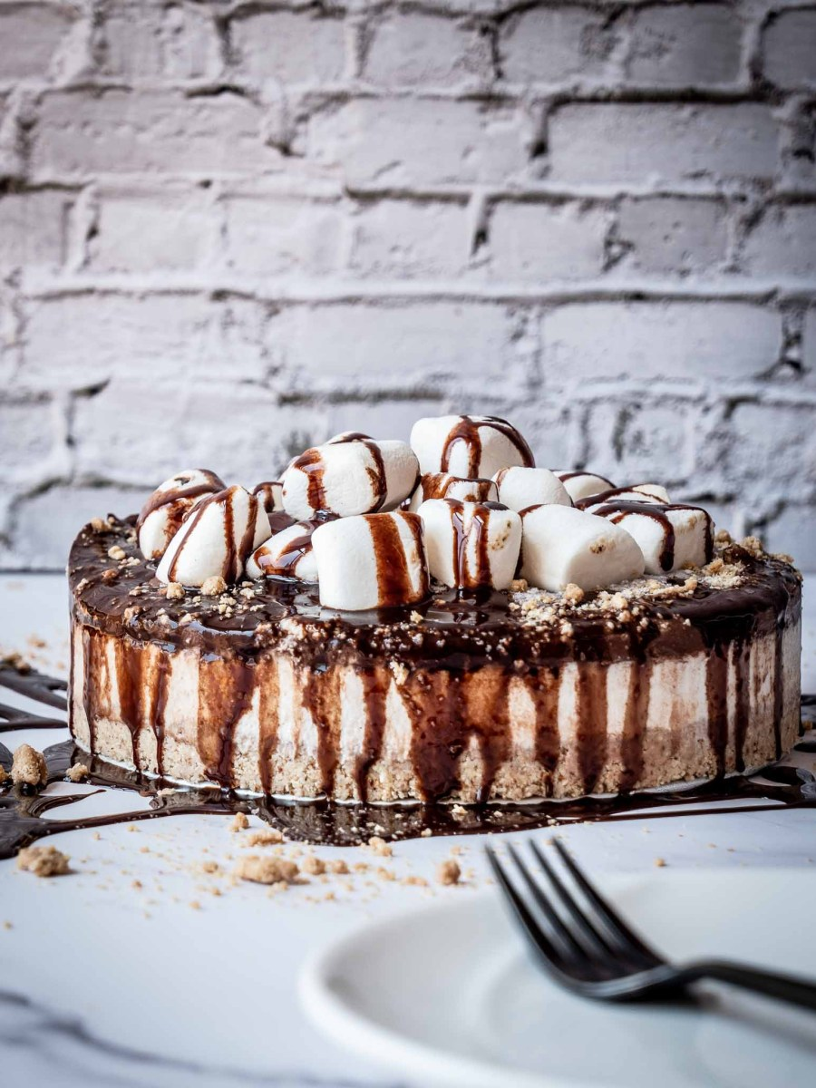 large vegan cheesecake with biscuit base, cream topping and chocolate drizzle dripping down sides with marshmallows on white table and white bricks