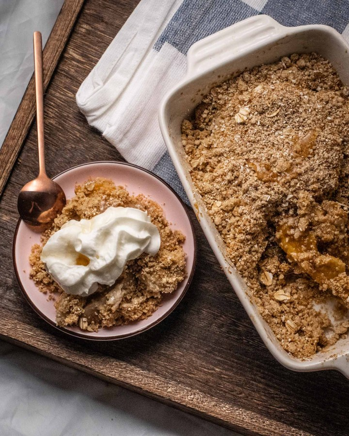 flatlay of apple oat crumble in rectangular ceramic baking dish next to plate filled with apple crumble topped with whipped cream