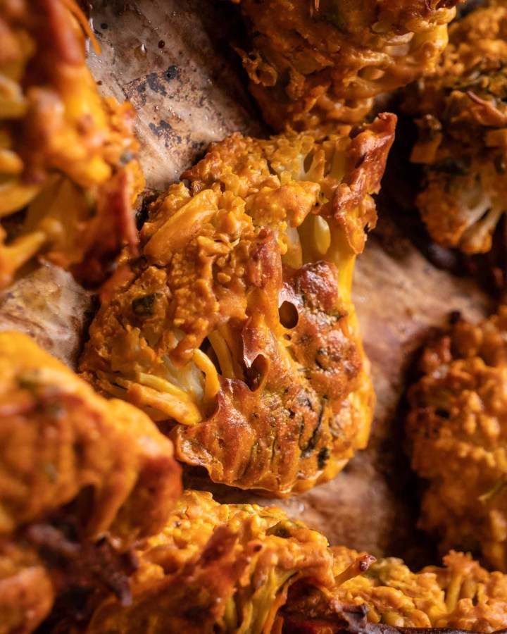 crispy baked cauliflower florets coated in golden crunchy chickpea flour batter on brown parchment paper on baking tray