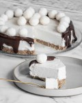 coconut chocolate cheesecake drizzled with chocolate dripping down edges and decorated with coconut candy balls