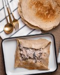 folded buckwheat flour pancake filled with mushrooms in cheese sauce