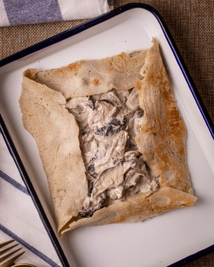 folded buckwheat galette crepe with top open filled with creamy vegan cheese mushrooms in white enamel tray lined with blue rim