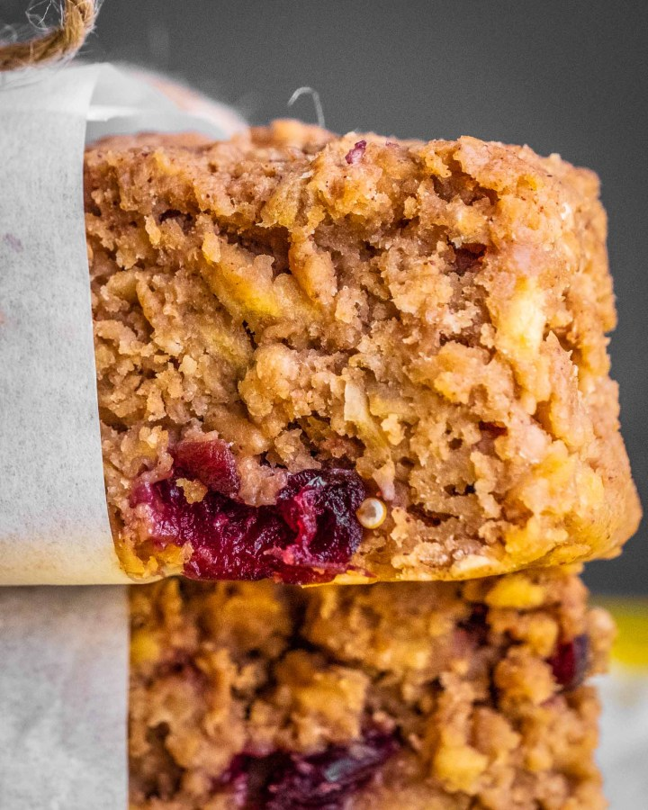 cherry protein bars stacked on top of each other half wrapped in white greaseproof paper and string