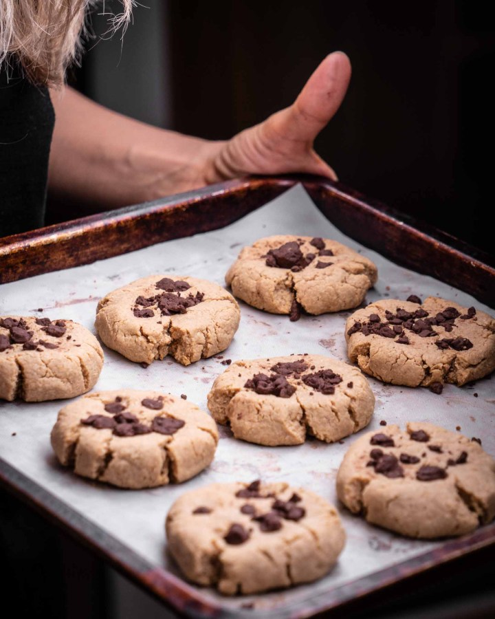 hands holding rustic metal baking tray filled with rows of chocolate chip cookies