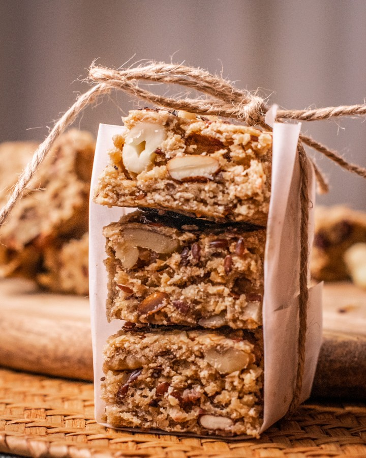 slices of chocolate and nut flapjacks stacked in threes and wrapped with white parchment paper and tied with brown string