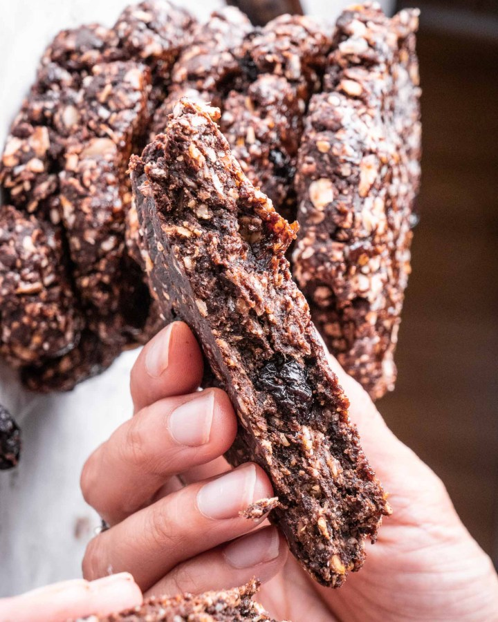 hand holding one half of broken chocolate oat cookie revealing chewy texture soft centre held above pile of cookies
