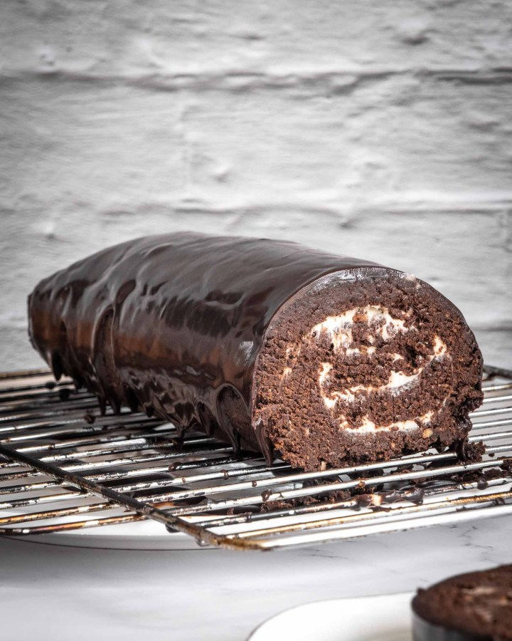 chocolate yule log cake drenched in  melted chocolate on metal rack with chocolate dripping off against white wall and on white marble table
