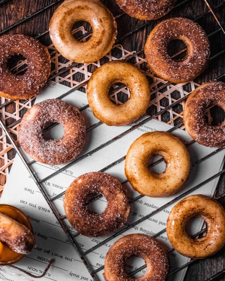 several golden cinnamon sugar donuts on wooden table with newspaper on metal rack