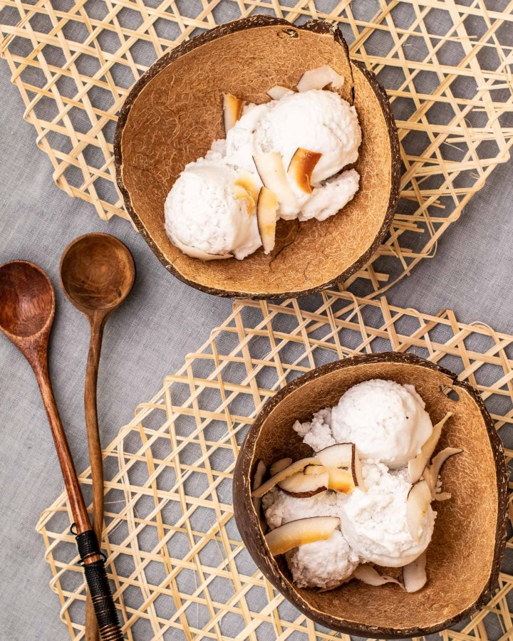 flatlay of 2 coconut bowls filled with coconut ice cream and coconut chips next to wooden spoons on straw mat