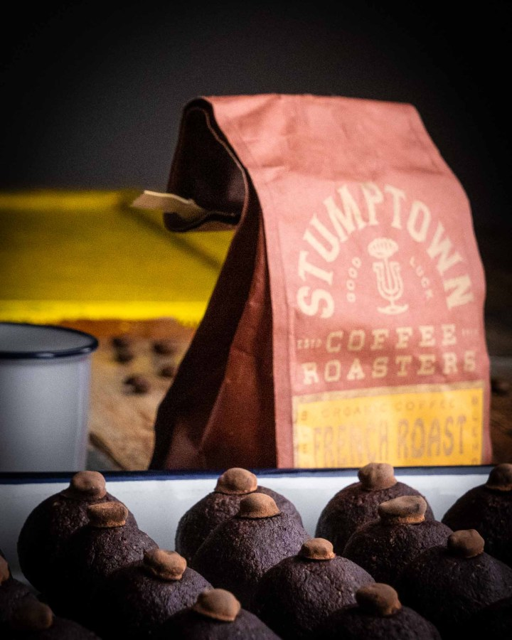 orange and gold paper bag of stumptown coffee next to white vintage espresso cup next to white vintage tray filled with coffee balls