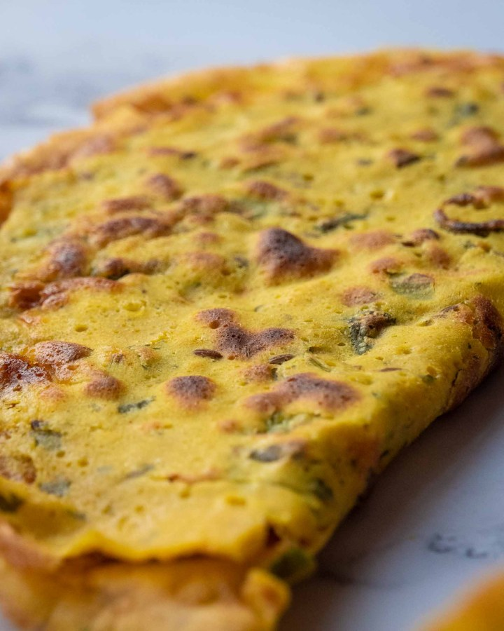 yellow besan chickpea flour crepe with gold brown bubbles and cumin and coriander appearing through surface