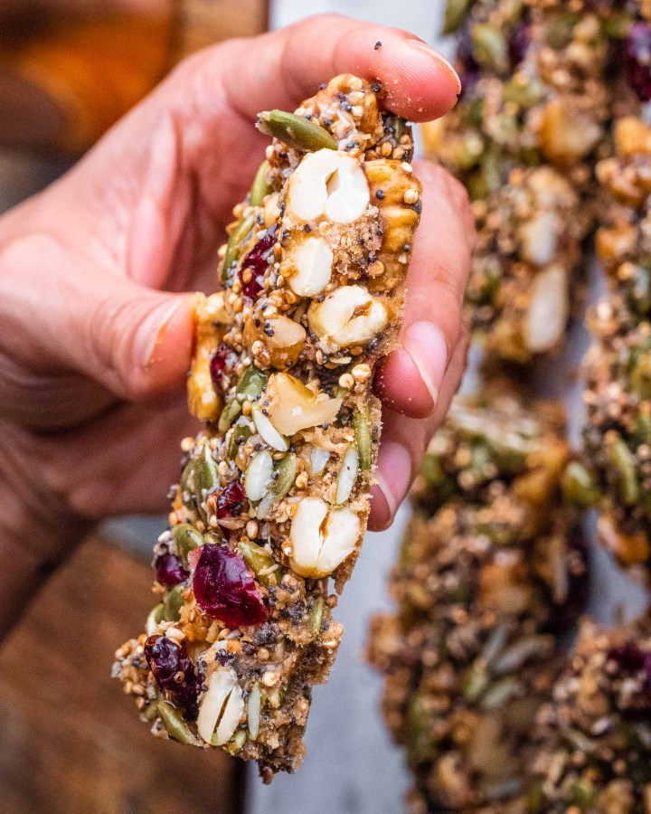 hand holding sliced crunchy granola bar showing centre filled with cashews, almonds, cranberries, pumpkin seeds, quinoa
