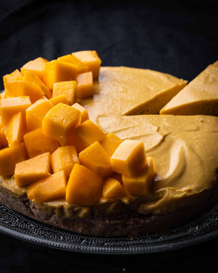 large round healthy mango cheesecake topped with large fresh mango chunks and slice being taken out with black background