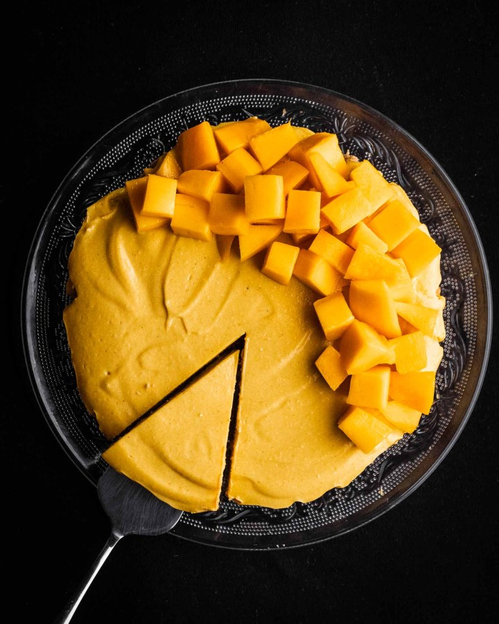 flatlay of round healthy no-bake vegan mango cheesecake with slice being taken out and half of cheesecake topped in mango
