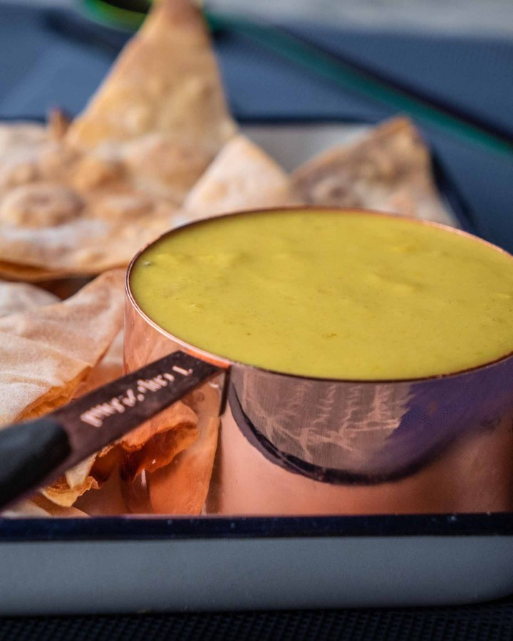 nacho cheese in copper tub next to pile of homemade crispy triangle nachos on blue mat