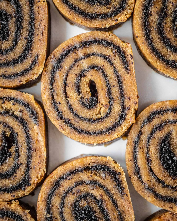 close up of poppy seed roll with brown gluten-free nut cake base and dark swirls of poppy seed jam within