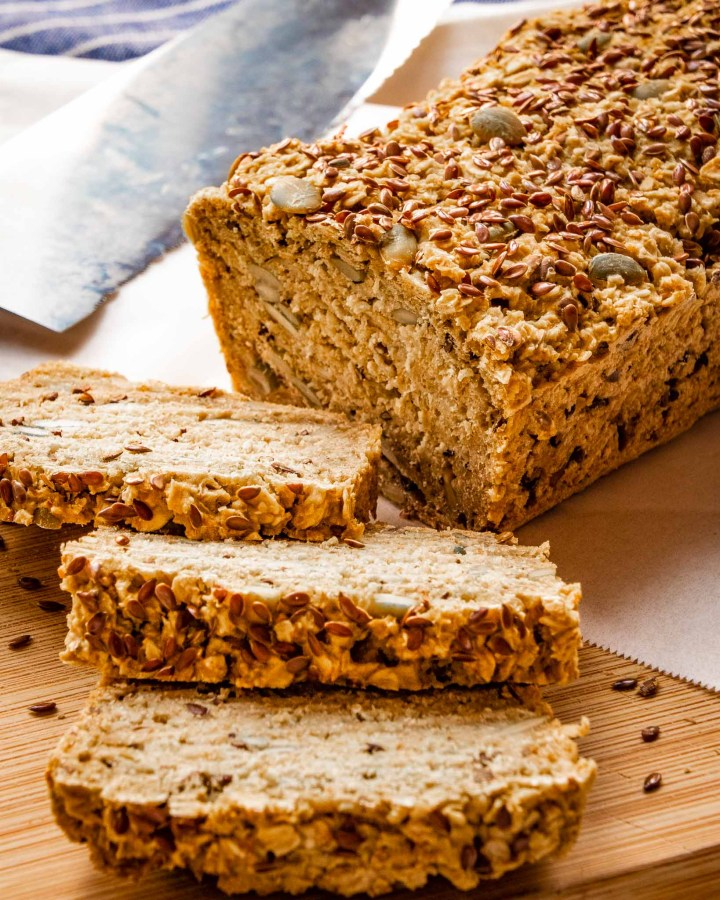 loaf of dense seeded oat porridge bread cut in slices on wooden board