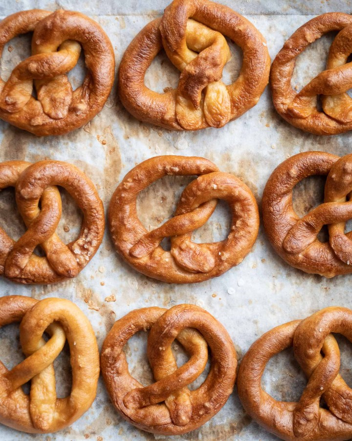 fresh bbaked soft pretzels on baking tray lined with white browned parchment paper