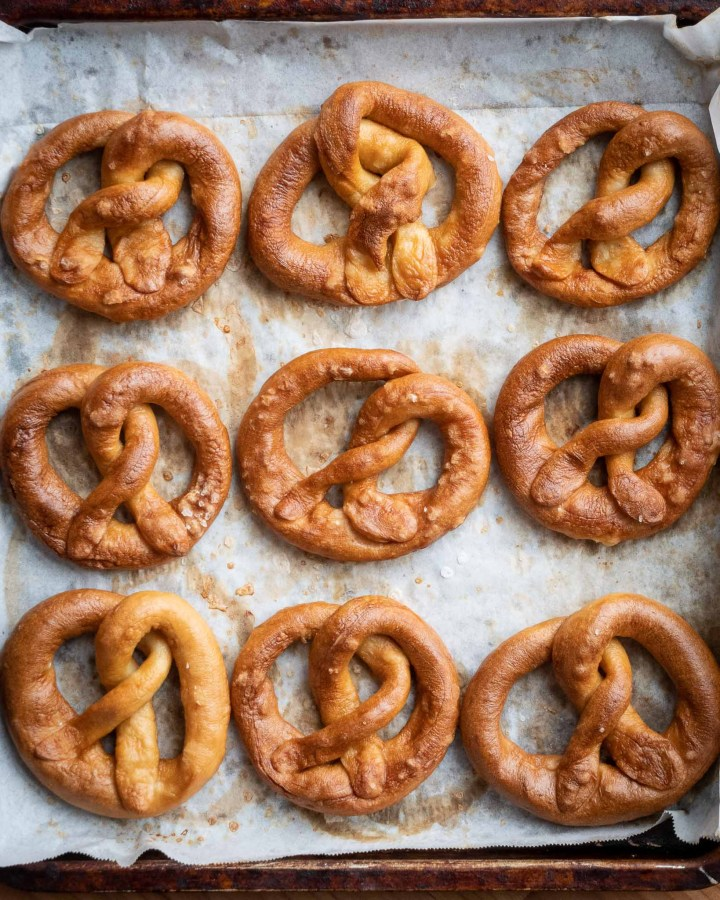 Flatlay of several golden brown pretzels in rows placed neatly on baking tray lined with greaseproof paper