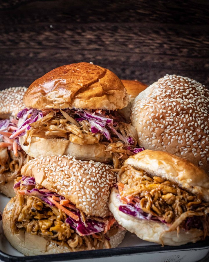 stack of pulled mushroom burgers in golden brioche buns and sesame topped buns filled with BBQ pulled vegan pork and purple coleslaw