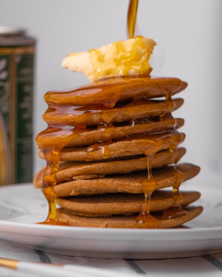 large stack of american style fluffy pancakes topped with lump of butter and drizzled generously with syrup dripping down sides