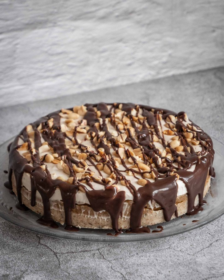 whole large cheesecake with biscuit base, fudgy caramel layer, whipped cream topped with drizzled chocolate and peanuts