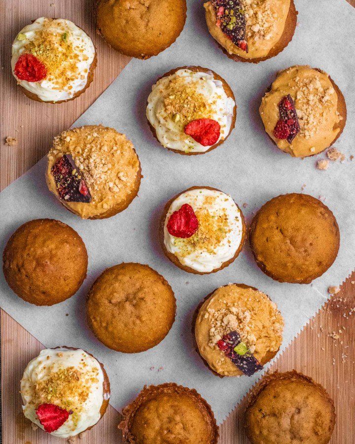 flatlay of 15 golden sweet potato cupcakes, some plain, others with white frosting or peanut butter and pistachios, strawberry or chocolate